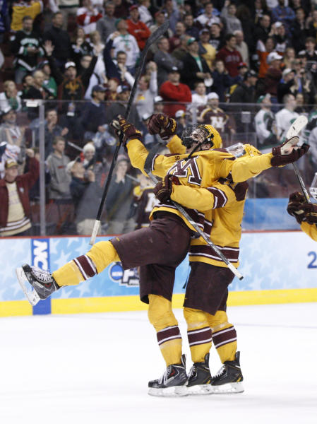 Minnesota's Justin Holl, left, reacts to his goal being ruled good with Sam Warning, right, behind him during the third period of an NCAA men's college hockey Frozen Four tournament game against North Dakota, Thursday, April 10, 2014, in Philadelphia. Minnesota won 2-1. (AP Photo/Chris Szagola)