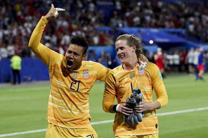 U.S. goalkeepers Adrianna Franch raises a pointer finger and Alyssa Naeher smiles on the field