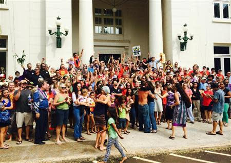 A crowd gathers in celebration on the steps of the historic Kauai County building in Lihue