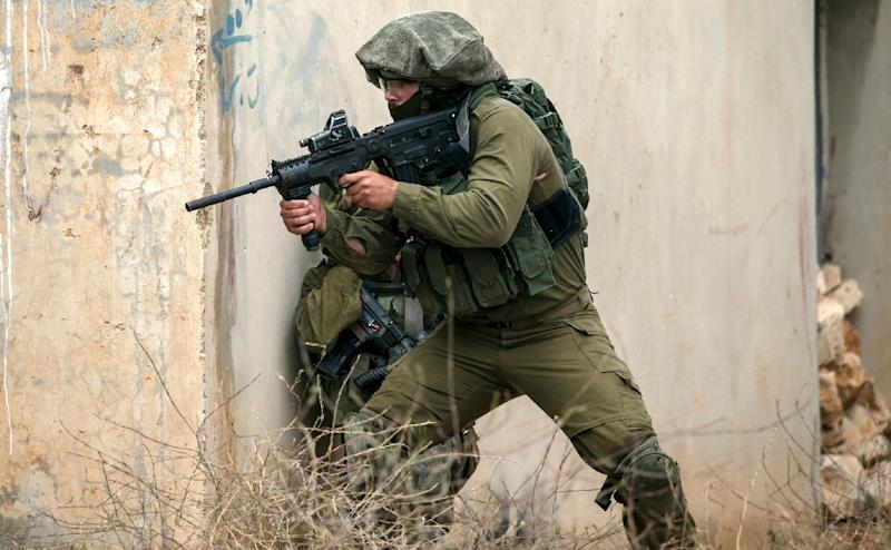 An Israeli soldier takes cover during clashes with Palestinian protesters following a demonstration against the expropriation of Palestinian land by Israel in the village of Kfar Qaddum near Nablus in the occupied West Bank on May 4 2018