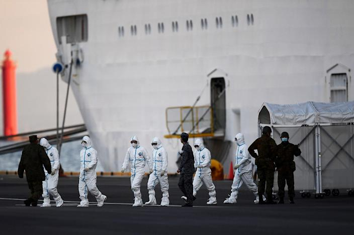 Image: People wearing protective suits walk from the Diamond Princess cruise ship, with around 3,700 people quarantined onboard due to fears of the new coronavirus, at the Daikoku Pier Cruise Terminal in Yokohama
