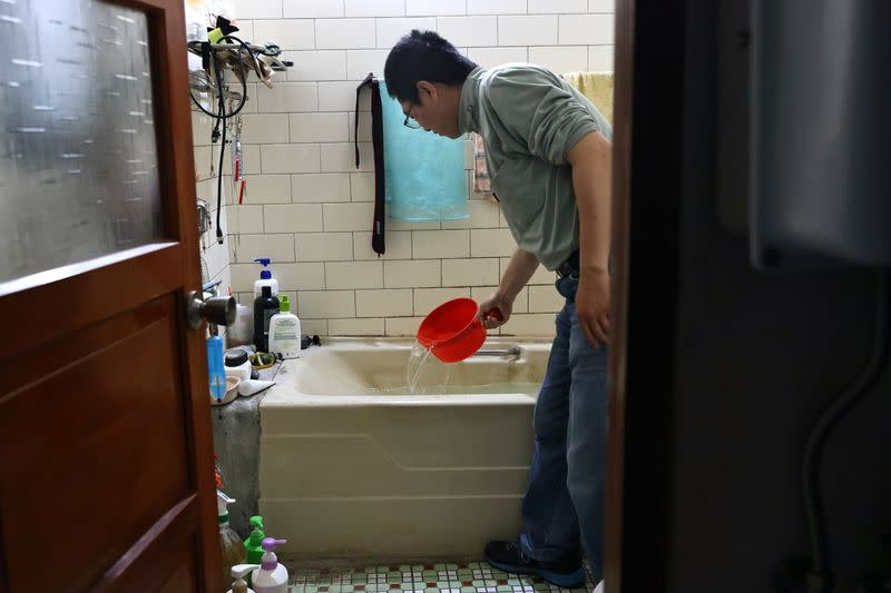 Man scoops water from a bathtub, where he stores water amid water rationing during an island-wide drought, in Hsinchu