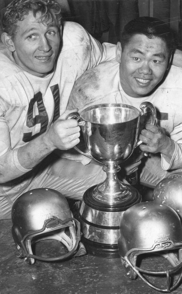 NOVEMBER 24, 1956 -- GREY CUP VICTORS --  A pair of happy Edmonton Eskimos stars hold the cup after convincing victory in Canadian football classic on Saturday. Jackie Parker, left, scored three touchdowns against the Montreal Alouettes at Varsity Stadium in Toronto while Normie Kwong played powerful game on line.   Photo by Harry McLorinan / The Globe and Mail