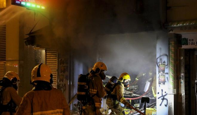 Firefighters put out a fire set by anti-government protesters in Mong Kok. Photo: K.Y. Cheng