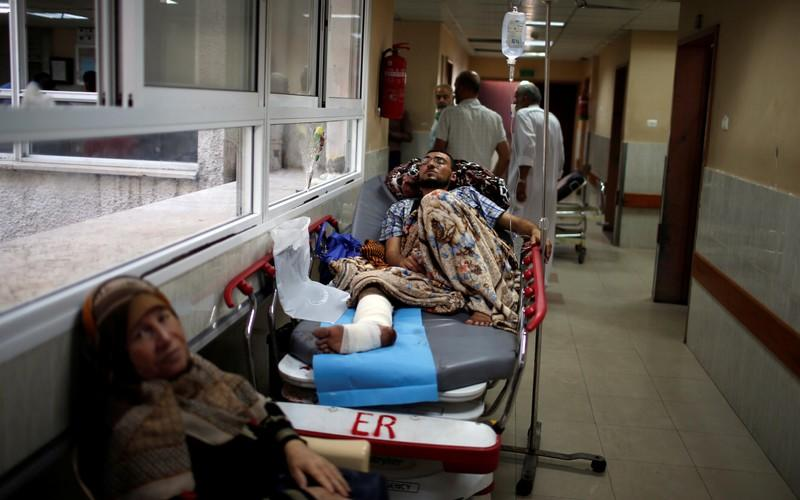 FILE PHOTO: Injured Palestinian lies on a bed in the corridor of a hospital in Gaza City