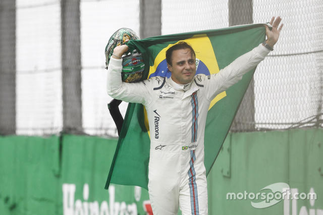 """Felipe Massa, Williams, carries a Brazilian flag as he walks back to his garage in tears after crashing <span class=""""copyright"""">Motorsport Images</span>"""