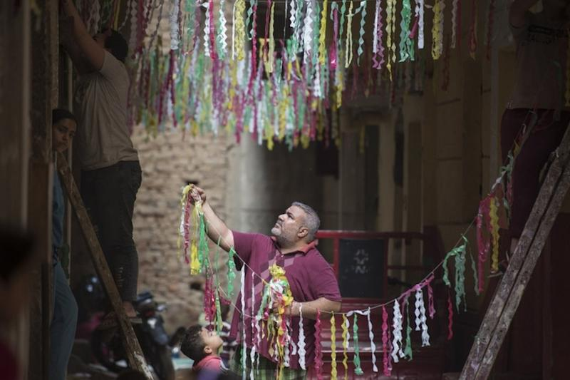 Two men hang strings of colourful paper decorations above a narrow street.