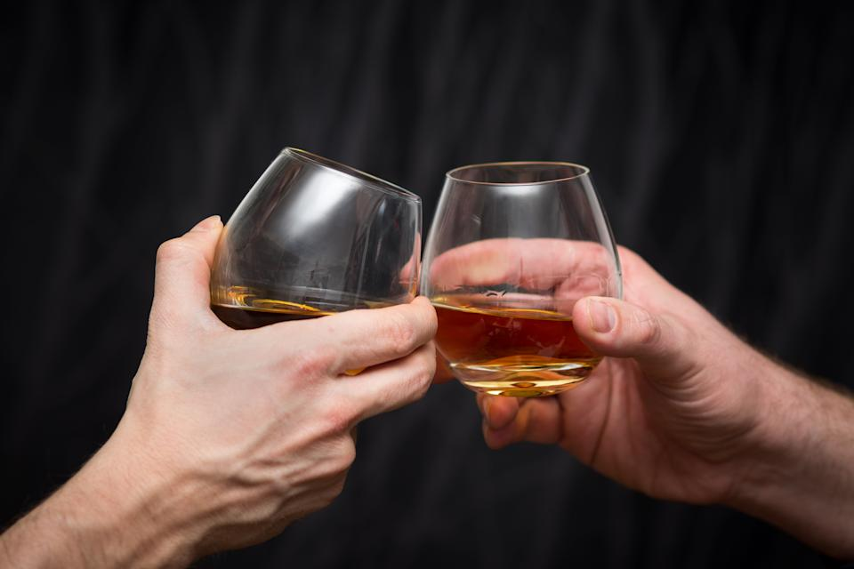 Two male right hands clinking whisky glasses on dark black background