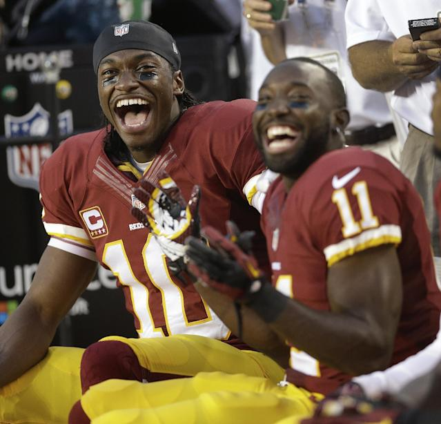 Washington Redskins quarterback Robert Griffin III, left, and wide receiver Aldrick Robinson laugh as they watch cornerback DeAngelo Hall score on an interception during the first half of an NFL football game against the Philadelphia Eagles in Landover, Md., Monday, Sept. 9, 2013. (AP Photo/Patrick Semansky)
