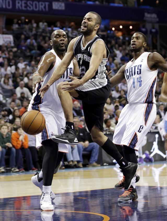 San Antonio Spurs' Tony Parker, center, is fouled as he drives past Charlotte Bobcats' Al Jefferson, left, and Michael Kidd-Gilchrist, right, during the first half of an NBA basketball game in Charlotte, N.C., Saturday, Feb. 8, 2014. (AP Photo/Chuck Burton)
