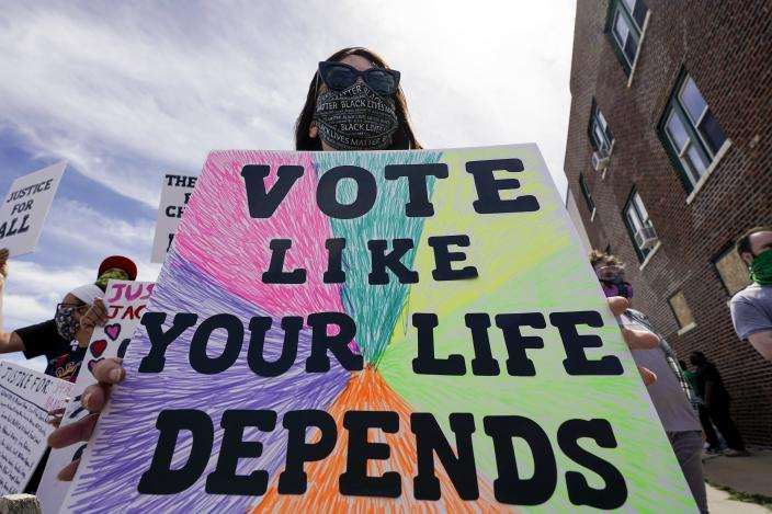 Amanda Becker holds a sign at a rally for Jacob Blake Saturday, Aug. 29, 2020, in Kenosha, Wis. (AP Photo/Morry Gash)