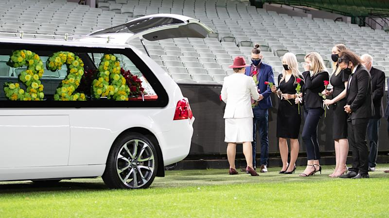 Family and mourners are pictured at the private memorial for Dean Jones.