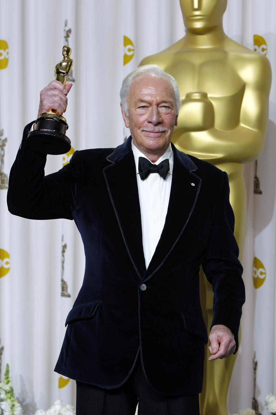 """FILE - Christopher Plummer poses with the Oscar for best supporting actor for his work in """"Beginners"""" during the 84th Academy Awards on Feb. 26, 2012, in the Hollywood section of Los Angeles. Plummer, the dashing award-winning actor who played Captain von Trapp in the film """"The Sound of Music"""" and at 82 became the oldest Academy Award winner in history, has died. He was 91. Plummer died Friday morning, Feb. 5, 2021, at his home in Connecticut with his wife, Elaine Taylor, by his side, said Lou Pitt, his longtime friend and manager. (AP Photo/Joel Ryan, File)"""