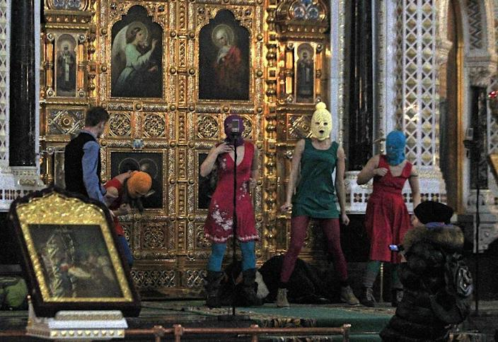 """In this Feb. 21, 2012 file photo, members of the Russian radical feminist group Pussy Riot try to perform at the Christ the Saviour Cathedral in Moscow. The trial of feminist punk rockers who chanted a """"punk prayer"""" against President Vladimir Putin from the pulpit of Russia's largest cathedral started in Moscow Friday, July 20, 2012 amid controversy over the prank that divided devout believers, Kremlin critics and ordinary Russians. (AP Photo/Sergey Ponomarev, File)"""