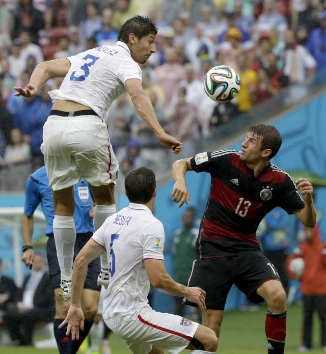 United States' Omar Gonzalez goes over Germany's Thomas Mueller to head the ball as United States' Matt Besler looks on during the group G World Cup soccer match between the USA and Germany at the Arena Pernambuco in Recife, Brazil, Thursday, June 26, 2014. (AP Photo/Ricardo Mazalan)
