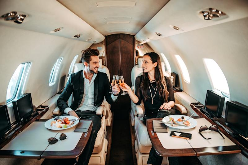 Rich couple making a toast with champagne glasses while eating canapes aboard a private jet.