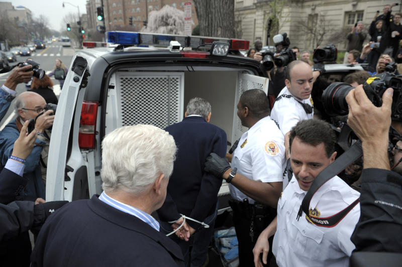 Actor George Clooney, center, followed Rep. Jim Moran, D-Va, lower left, are placed into a police vehicle after being arrested during a protest at the Sudan Embassy in Washington, Friday, March 16, 2012. The demonstrators are protesting the escalating humanitarian emergency in Sudan that threatens the lives of 500,000 people. (AP Photo/Cliff Owen)