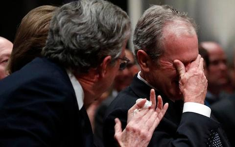 Former President George W Bush cries after speaking during the state funeral for his father - Credit: Getty