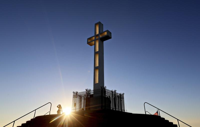 People gather in the late evening sun around the massive cross sitting atop the Mt. Soledad War Memorial in La Jolla