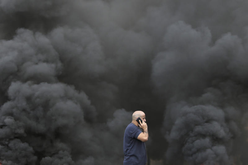 A man speaks on his smartphone while walking by black smoke from burning tires that were set on fire to block a road during a protest against government's plans to impose new taxes in Beirut, Lebanon, Friday, Oct. 18, 2019. The protests erupted over the government's plan to impose new taxes during a severe economic crisis, with people taking their anger out on politicians they accuse of corruption and decades of mismanagement. (AP Photo/Hassan Ammar)
