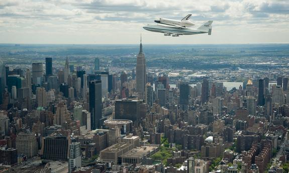 Space shuttle Enterprise, mounted atop a NASA 747 Shuttle Carrier Aircraft (SCA), is seen as it flies near the Empire State Building, Friday, April 27, 2012, in New York.
