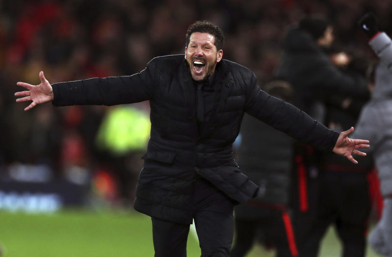 Atletico Madrid manager Diego Simeone celebrates after Marcos Llorente scored his side's second goal of the game during a second leg, round of 16, Champions League soccer match between Liverpool and Atletico Madrid at Anfield stadium in Liverpool, England, Wednesday, March 11, 2020. (Peter Byrne/PA via AP)