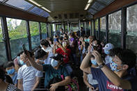 Passengers take photos from a Peak Tram during a tram journey in Hong Kong on June 17, 2021. Hong Kong's Peak Tram is a fixture in the memories of many residents and tourists, ferrying passengers up Victoria Peak for a bird's eye view of the city's many skyscrapers. (AP Photo/Vincent Yu)
