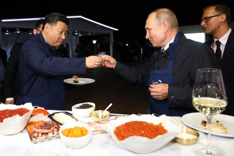 "Russian President Vladimir Putin toasts with his Chinese counterpart Xi Jinping as they tasted pancakes they cooked while visiting ""The Far East Street"" exhibition"