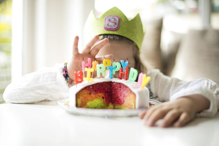 An image of a child behind a birthday cake.