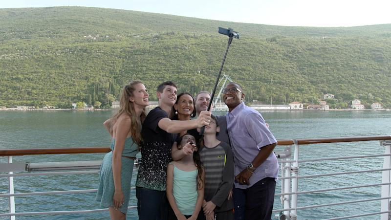 "This undated photo provided by Carnival Corporation shows hosts Andrea Feczko on the far left and Tommy Davidson on the far right taking a selfie with the Geoghegan family on a Mediterranean cruise to Greece. Feczko and Davidson are hosts of ""Vacation Creation,"" one of three new shows produced by Carnival Corp., showcasing vacation and travel connected to cruising. ""Vacation Creation,"" which will begin airing on The CW network this fall, features personalized vacations for individuals, couples or families who have faced hardship or are in need of hope or quality time together. (Carnival Corporation via AP)"