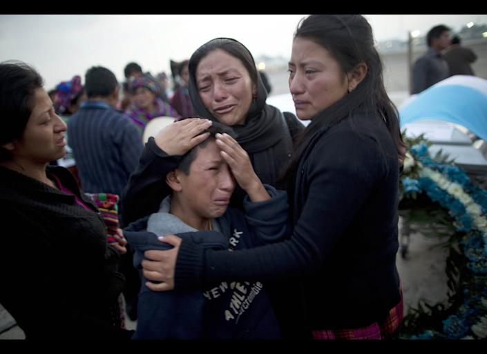 Relatives mourn next to the coffin containing the remains of Jose Yovanny Bocel at an Air Force base in Guatemala City , Wednesday, March 21, 2012. The remains of 11 Guatemalan citizens were repatriated from Mexico Wednesday, part of 193 bodies found in the northern Mexico Tamaulipas state in 26 mass graves in April 2011. (AP Photo/Rodrigo Abd)