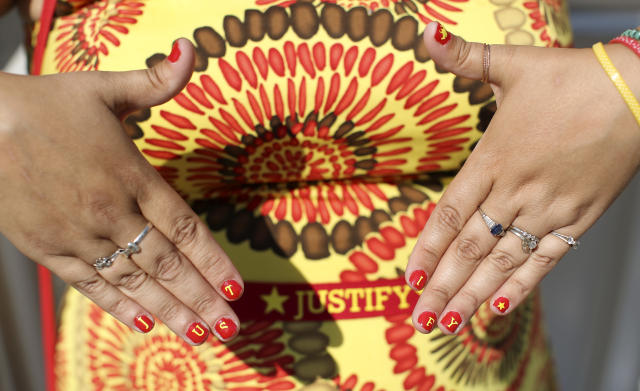A horse racing fan shows off her finger nails painted with Triple Crown hopeful Justify's name before the 150th running of the Belmont Stakes horse race, Saturday, June 9, 2018, in Elmont, N.Y. (AP Photo/Mary Altaffer)
