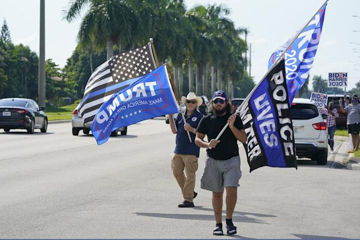 Trump supporters wave flags in front of a small group of Biden backers in Miramar, Fla.
