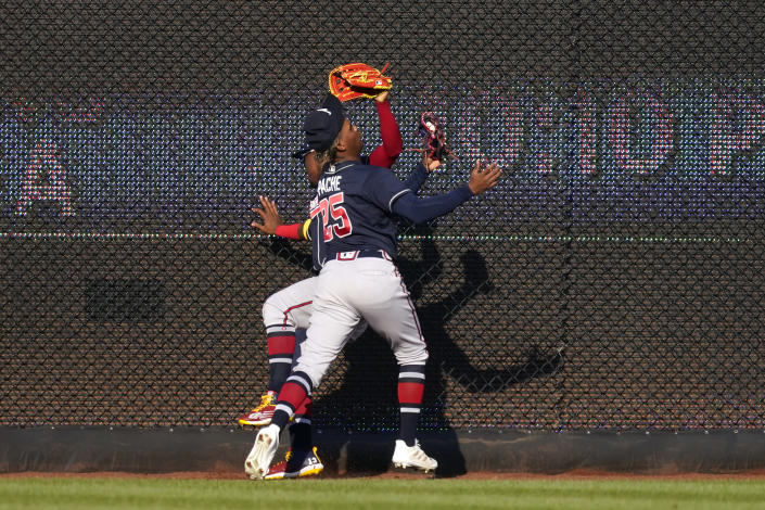 Atlanta Braves center fielder Cristian Pache (25) collides with right fielder Ronald Acuna Jr. as he catches Washington Nationals' Starlin Castro's fly ball in the sixth inning of an opening day baseball game at Nationals Park, Tuesday, April 6, 2021, in Washington. (AP Photo/Alex Brandon)