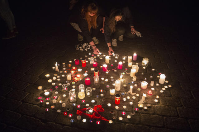 <p>In this Saturday, April 7, 2018 photo people light candles in Muenster, western Germany where a van crashed into people drinking outside a popular bar von on Saturday afternoon, killing two people and injuring 20 others before the driver of the vehicle shot and killed himself inside it. (Photo: Friso Gensch/dpa via AP) </p>