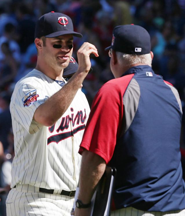Minnesota Twins manager Ron Gardenhire, right, celebrates with Joe Mauer after their 4-3 win over the Chicago White Sox in a baseball game, Saturday, June 21, 2014, in Minneapolis. Mauer had two RBI's. (AP Photo/Jim Mone)