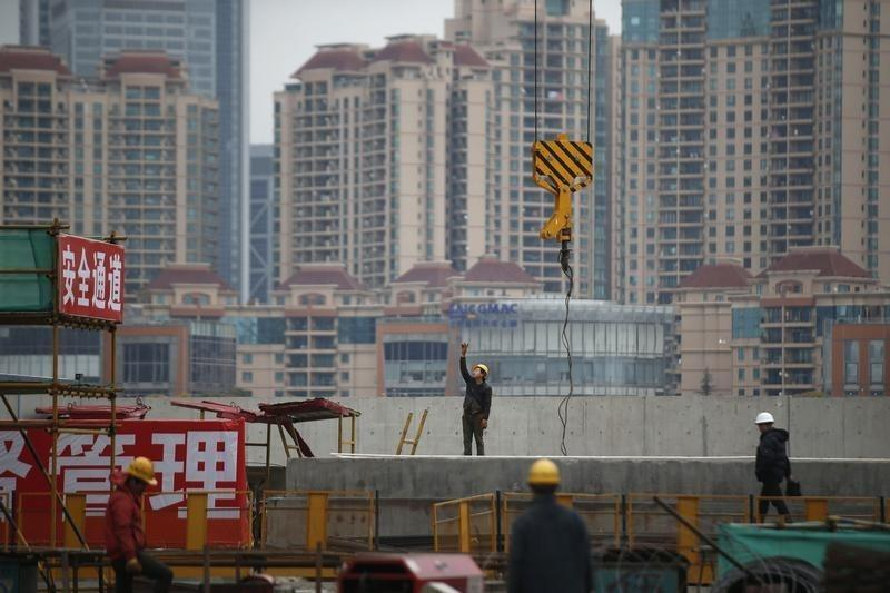 Labourers work at a construction site for a new building in Shanghai