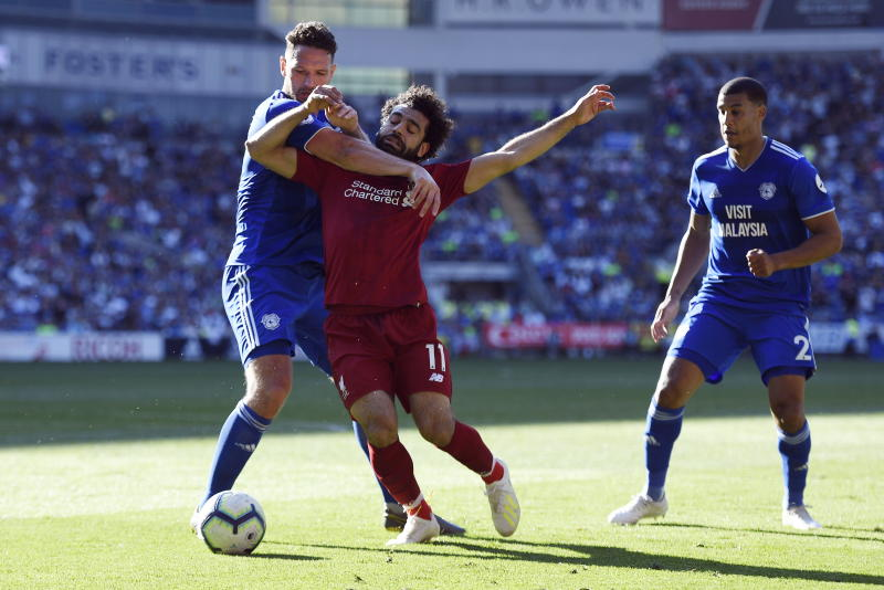 WO00. Cardiff (United Kingdom), 21/04/2019.- Liverpool's Mo Salah (C) is fouled by Cardiff's Sean Morrison (L) for a penalty during their English Premier League game at Cardiff City Stadium, Cardiff, Britain, 21 April 2019. (Reino Unido) EFE/EPA/WILL OLIVER EDITORIAL USE ONLY. No use with unauthorized audio, video, data, fixture lists, club/league logos or 'live' services. Online in-match use limited to 120 images, no video emulation. No use in betting, games or single club/league/player publications