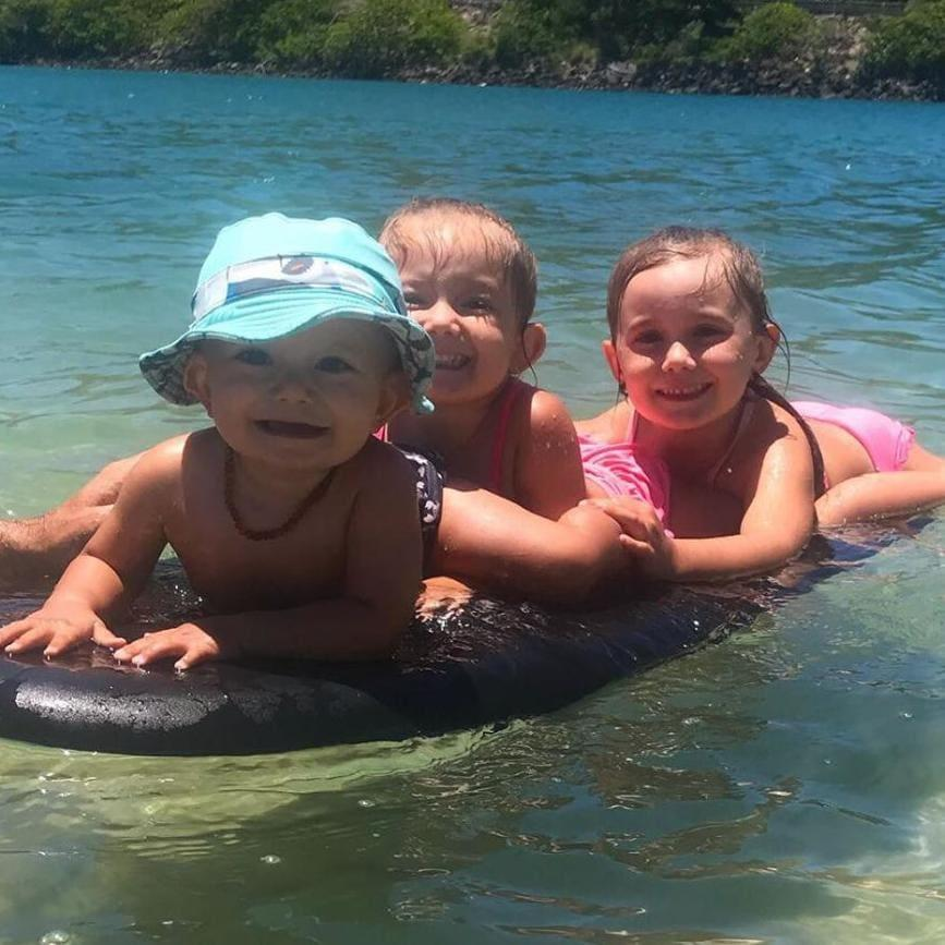 Aaliyah, Laianah and Trey playing the water on a surfboard