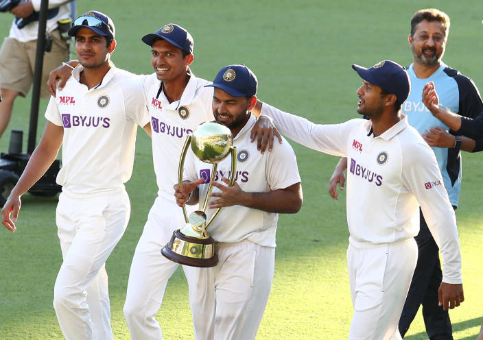India's Rishabh Pant carries the trophy as he celebrates with his teammates after defeating Australia by three wickets on the final day of the fourth cricket test at the Gabba, Brisbane, Australia, Tuesday, Jan. 19, 2021.India won the four test series 2-1. (AP Photo/Tertius Pickard)