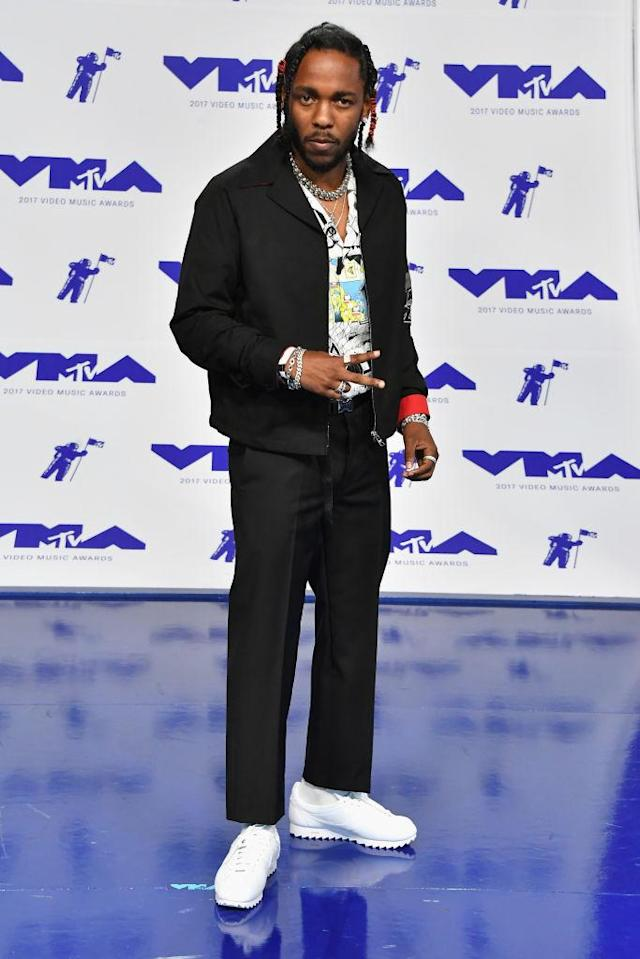 <p>Kendrick Lamar paired white sneakers with a black suit and colorful collared shirt. (Photo: AP) </p>