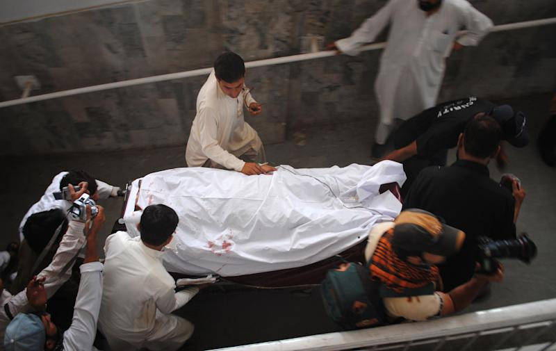 Hospital staff and relatives transport an injured female polio worker at a local hospital in Peshawar, Pakistan, Tuesday, May 28, 2013. Police say gunmen in Pakistan have shot dead a female polio worker and wounded another in the northwest, police said. (AP Photo/Mohammad Sajjad)