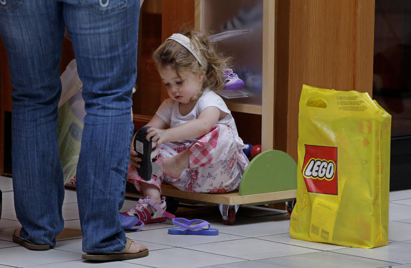 In this Wednesday, May 30, 2012, photo, Alexis Osgood, 2, sits down outside a shoe store with her LEGO bag next to her to try on a pair of sneakers as her mother Caitlin looks on at the South Shore Mall in Braintree, Mass. U.S. retail sales declined in April and May, pulled down by a sharp drop in gas prices. But even after excluding volatile gas sales, consumers increased their spending only modestly. (AP Photo/Stephan Savoia)