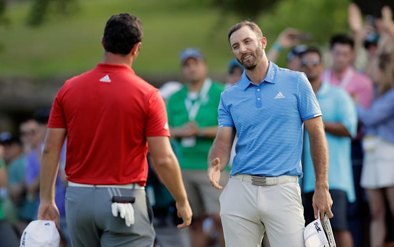 Dustin Johnson shakes hands with Rahm - Credit: AP