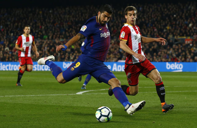 FC Barcelona's Luis Suarez, left, in action against Girona's Pere Pons during the Spanish La Liga soccer match between FC Barcelona and Girona at the Camp Nou stadium in Barcelona, Spain, Saturday, Feb. 24, 2018. (AP Photo/Manu Fernandez)