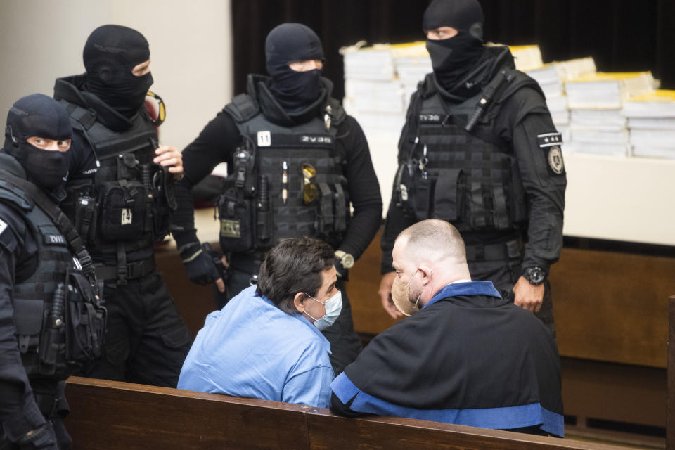 Defendant Marian Kocner, center left, and his lawyer Marek Para sit at the Supreme Court in Bratislava, Slovakia, Tuesday, June 15, 2021. Slovakia's appeals court has dismissed a lower court verdict that acquitted a businessman accused of masterminding the 2018 slayings of an investigative journalist who had written about him and the journalist's fiancee. The verdict by Slovakia's Supreme Court means that the case now returns to the Specialized Criminal Court in Pezinok that ruled in September to clear the businessman, Marian Kocner, and one co-defendant of murder in the killings of journalist Jan Kuciak and his fiancee, Martina Kusnirova, both 27. (Jaroslav Novak/TASR via AP)
