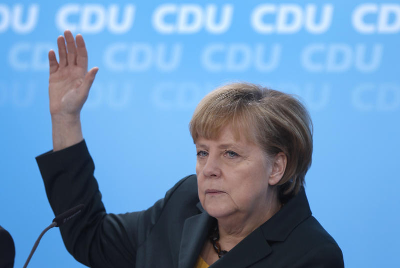 German Chancellor and chairwoman of the German Christian Democratic Party, Angela Merkel votes on the meeting agenda during a party's meeting about a coalition agreement with the German Social Democrats in Berlin, Germany, Monday, Dec. 9, 2013. (AP Photo/Michael Sohn)