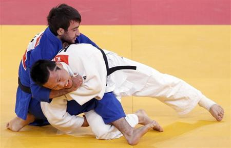 South Korea's Wang Ki-Chun fights with Russia's Mansur Isaev in men's -73kg semi-final judo match at London 2012 Olympic Games