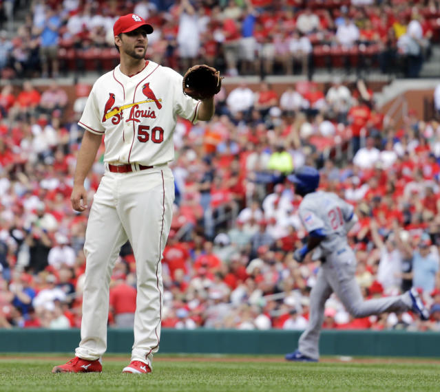 St. Louis Cardinals starting pitcher Adam Wainwright, left, waits for a new ball as Chicago Cubs' Junior Lake rounds the bases after hitting a solo home run during the first inning of a baseball game Saturday, April 12, 2014, in St. Louis. (AP Photo/Jeff Roberson)