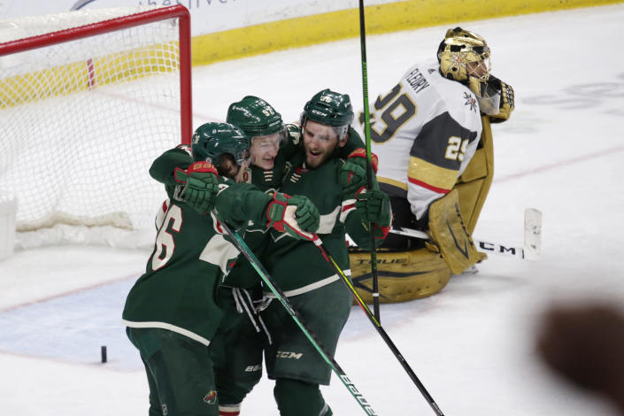 Minnesota Wild left wing Kirill Kaprizov (97) celebrates his goal with right wing Mats Zuccarello (36) and right wing Ryan Hartman (38) as Vegas Golden Knights goaltender Marc-Andre Fleury (29) reacts during the third period during an NHL hockey game Wednesday, May 5, 2021, in St. Paul, Minn. The Golden Knights won 3-2 in overtime. (AP Photo/Andy Clayton-King)